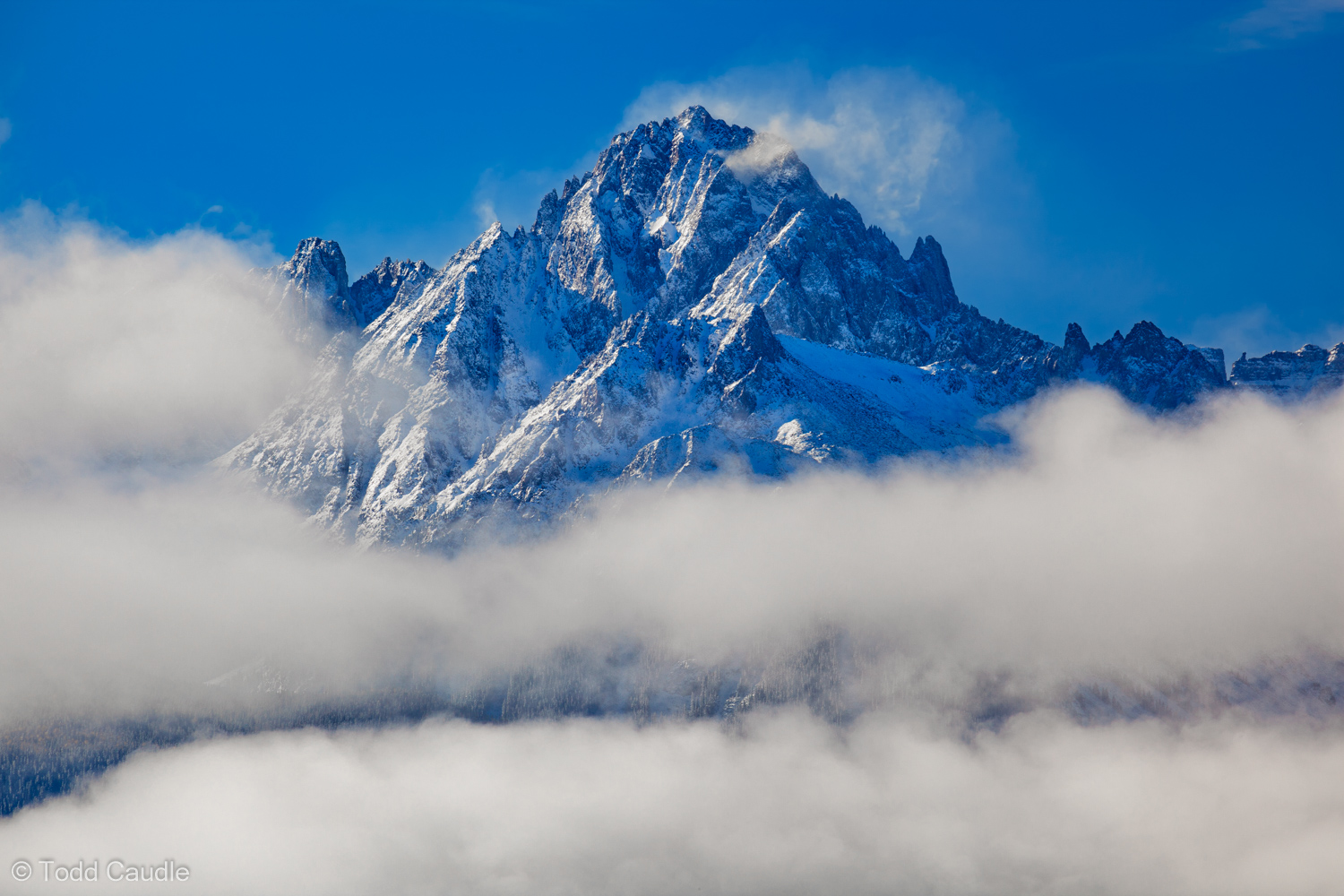 After a night of snow, morning clouds form around the impressive, serrated ridges of Mount Sneffels in the Sneffels Range near...