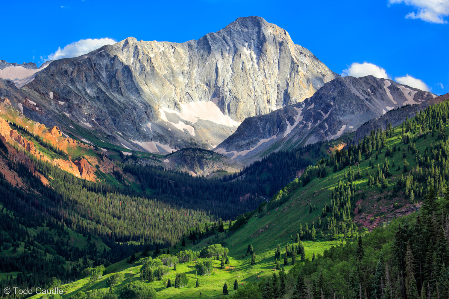 A wide-open view up the Capitol Creek Valley shows the dramatic south face of Capitol Peak, one of the most difficult of Colorado...