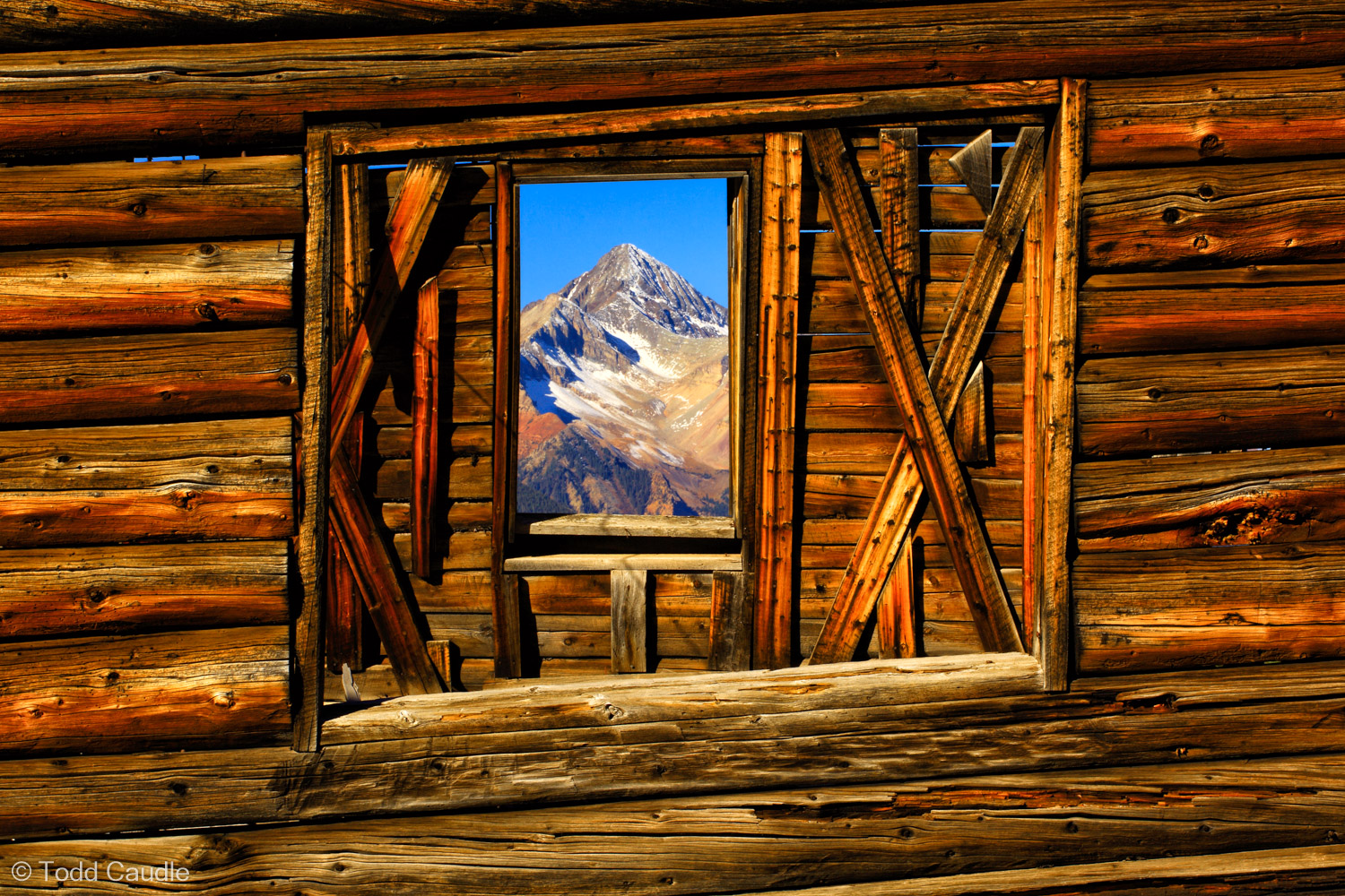 Wilson Peak looks like a picture hanging on a wall in this view through dual windows in an abandoned ghost town cabin.