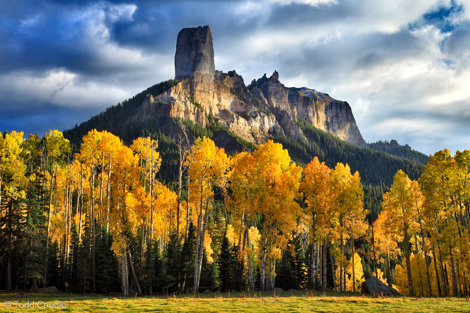 Chimney Rock and Courthouse Mountain rise above a forest of gold aspens and cool pine trees in the Cimarrons. The meadow in the...