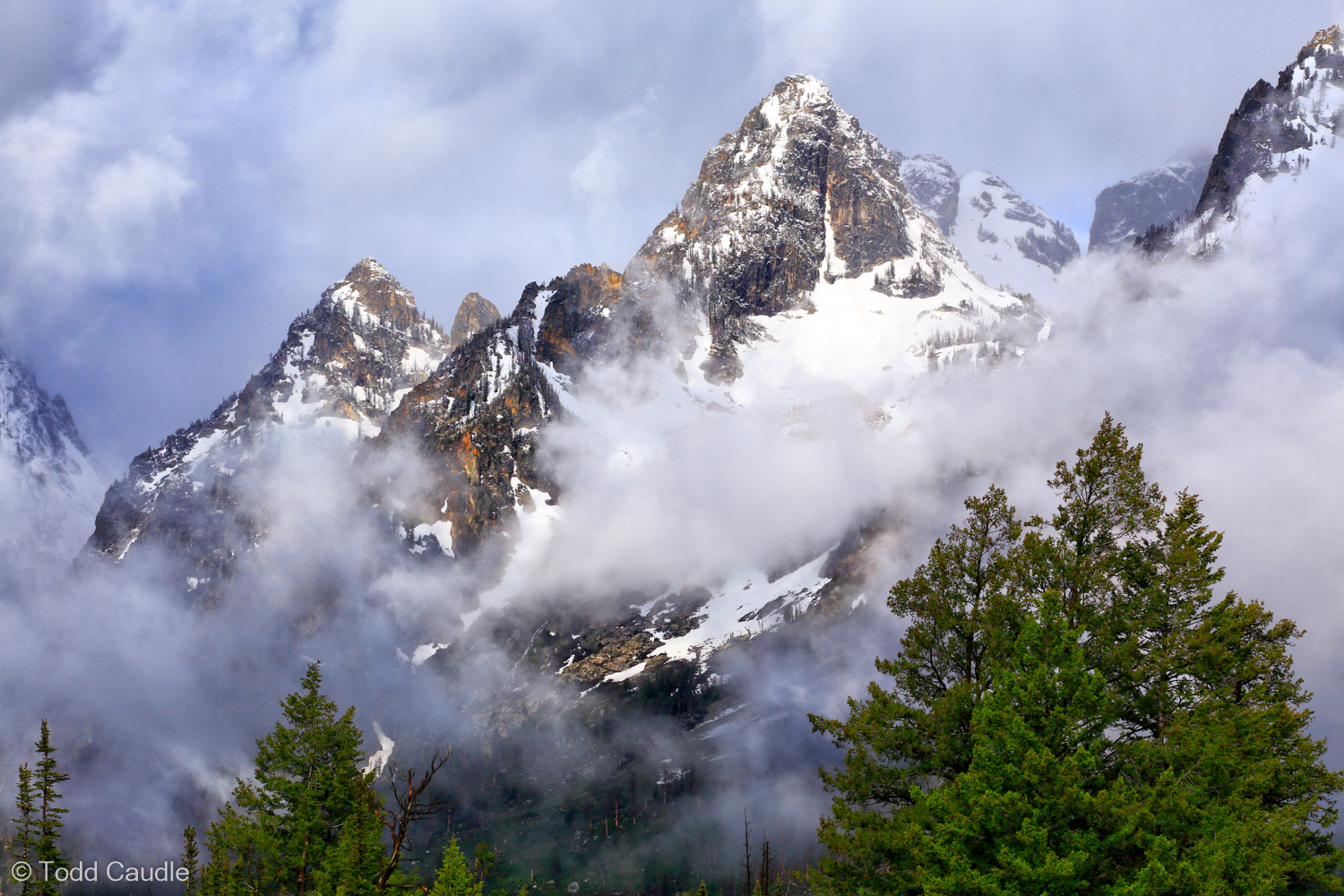 Morning clouds swirl around peaks of the Teton Range on an early-summer day.