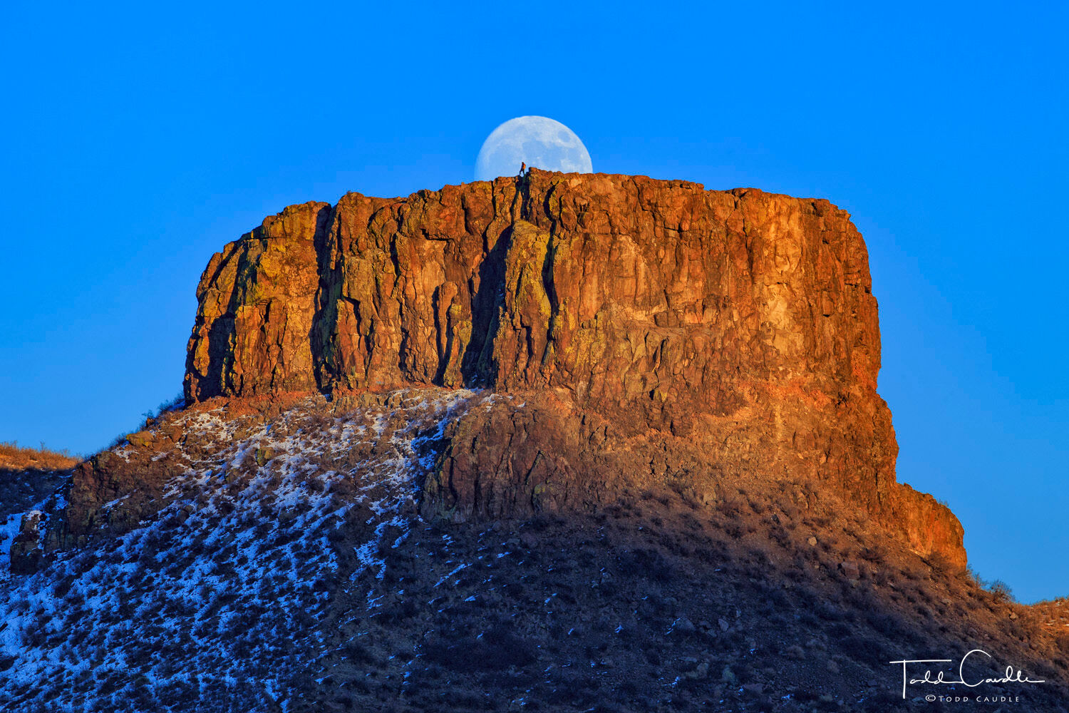 A hiker (ahem, my wife) stands atop Castle Rock at sunset as the moon rises behind her.